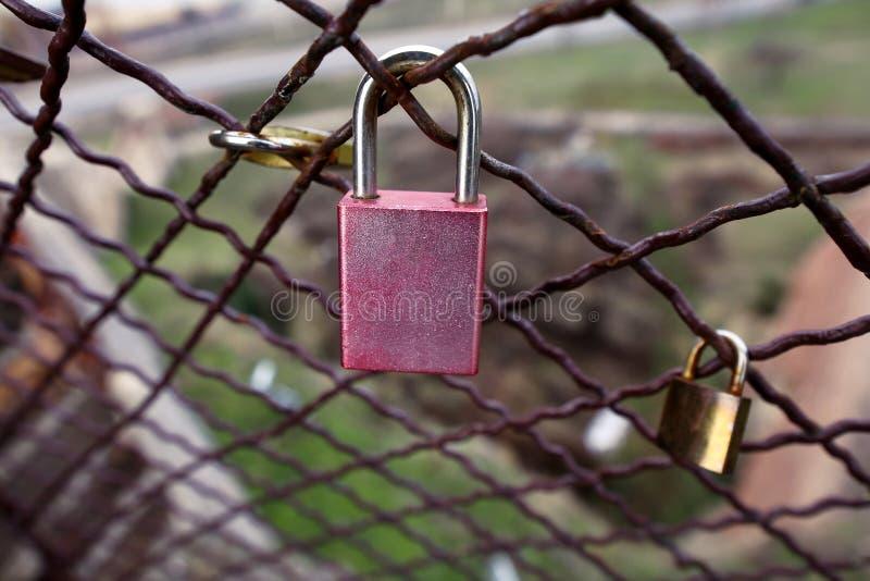 作为永恒爱的标志的闭合的爱锁与篱芭的在桥梁在城市 恋人挂锁桥梁的作为连接的标志 免版税库存图片