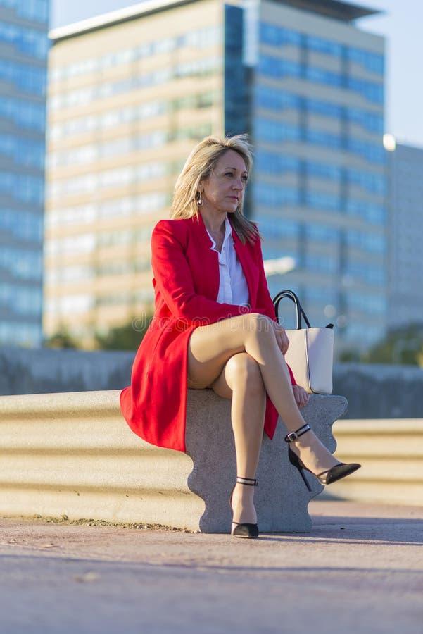 低角度观点的红色夹克的一名典雅的白肤金发的妇女坐长凳户外,当看在好日子时 库存图片