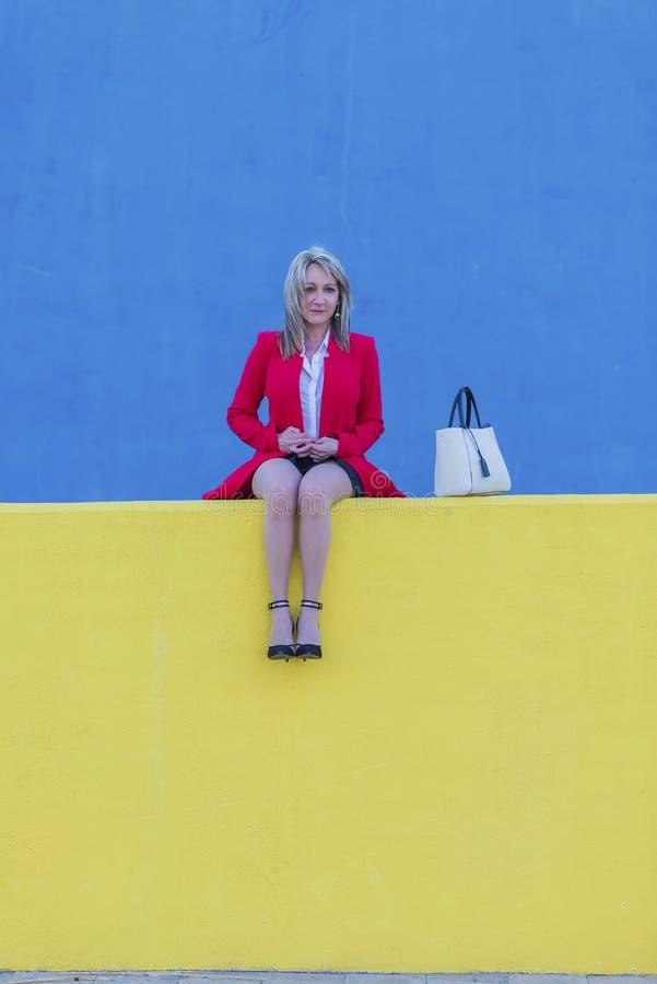 低角度观点的红色夹克的一名典雅的白肤金发的妇女坐长凳户外,当看照相机在好日子时 免版税库存照片