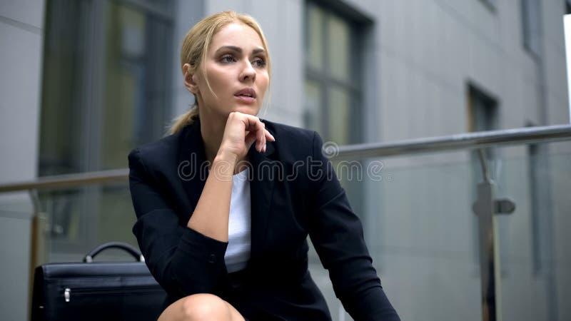 体贴的白肤金发的女实业家坐长凳、问题或者重音在工作 免版税库存图片