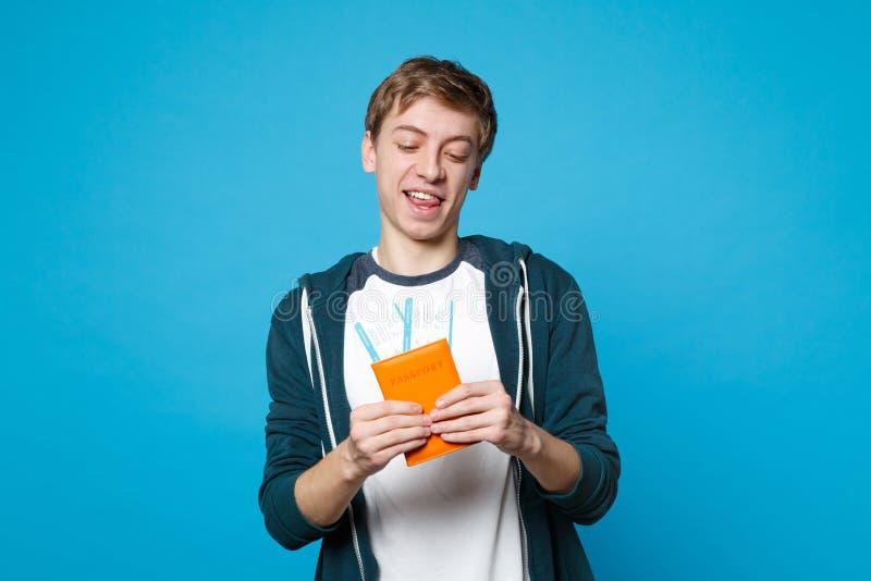 便服的举行快乐的滑稽的年轻人,看在护照,在蓝色墙壁上隔绝的登机牌票 库存图片
