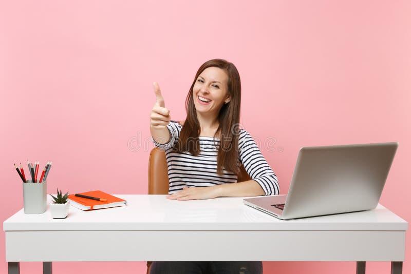 便服的微笑的妇女显示赞许工作在有被隔绝的当代个人计算机膝上型计算机的白色书桌坐粉红彩笔 免版税库存图片