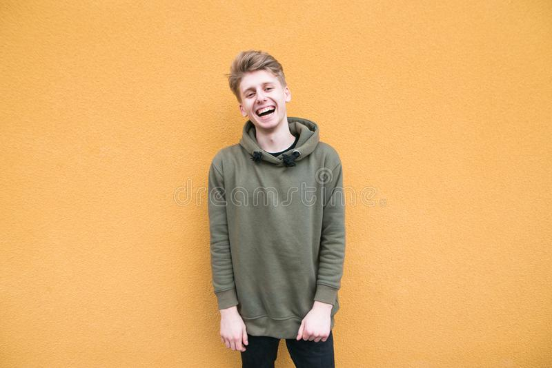 便服的愉快的年轻人在橙色墙壁和微笑的背景站立 免版税库存照片
