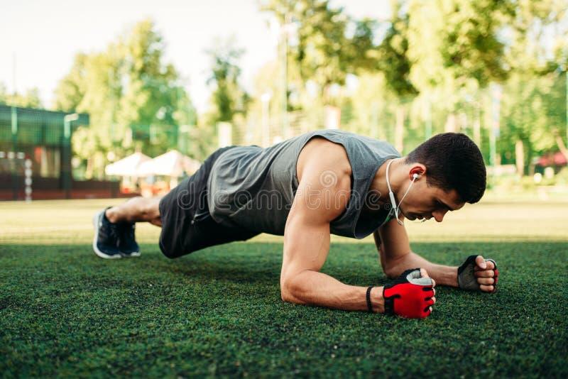 供以人员做在室外的草的俯卧撑锻炼 免版税库存图片