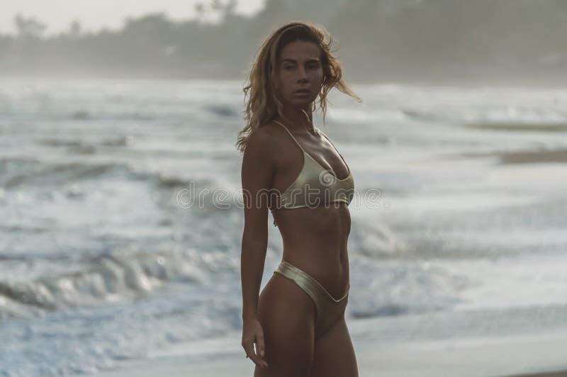 俏丽的年轻模型在平衡站立二分之一轮对照相机,摆在海洋海滩 免版税库存图片