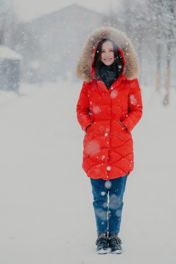 俏丽的全长垂直的射击女服红色冬天夹克,牛仔裤,并且起动,在口袋,在街道上的立场保留手 免版税库存照片