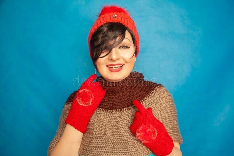 俏丽的深色的女孩佩带的时尚红色被编织的冬天gat和温暖的美丽的手套在蓝色演播室坚实背景 库存图片