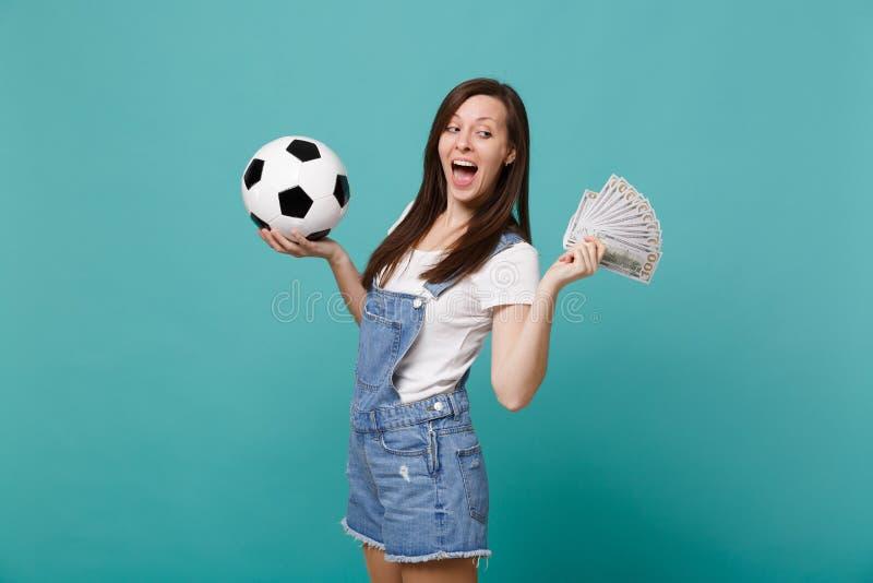 俏丽的滑稽的与足球的年轻女人足球迷支持喜爱的队,金钱爱好者在美元钞票现金的 免版税库存图片