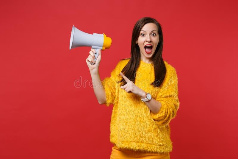 保持嘴的黄色毛皮毛线衣的震惊年轻女人大开,指向在明亮隔绝的扩音机的食指 图库摄影