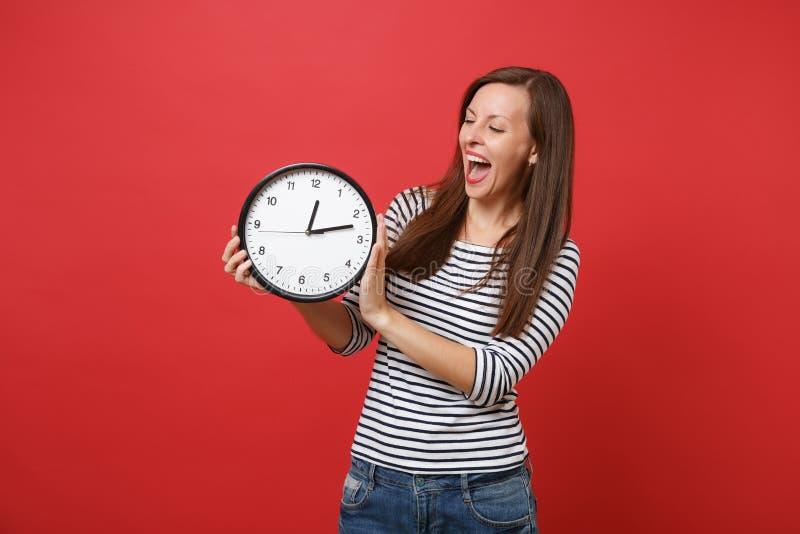 保留嘴大开看的镶边衣裳的快乐的年轻女人惊奇,拿着圆的时钟被隔绝  免版税库存照片