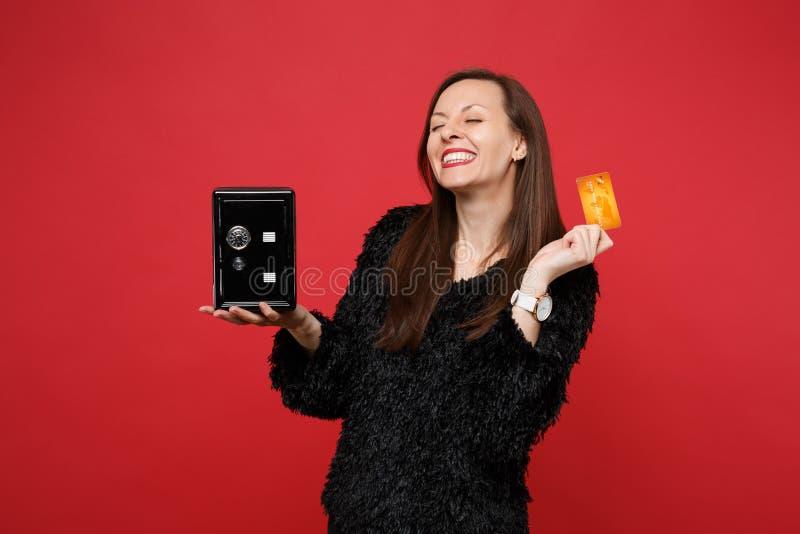 保留眼睛的黑毛皮毛线衣的愉快的微笑的年轻女人关闭了,举行金属银行安全为金钱储积,信用 免版税图库摄影