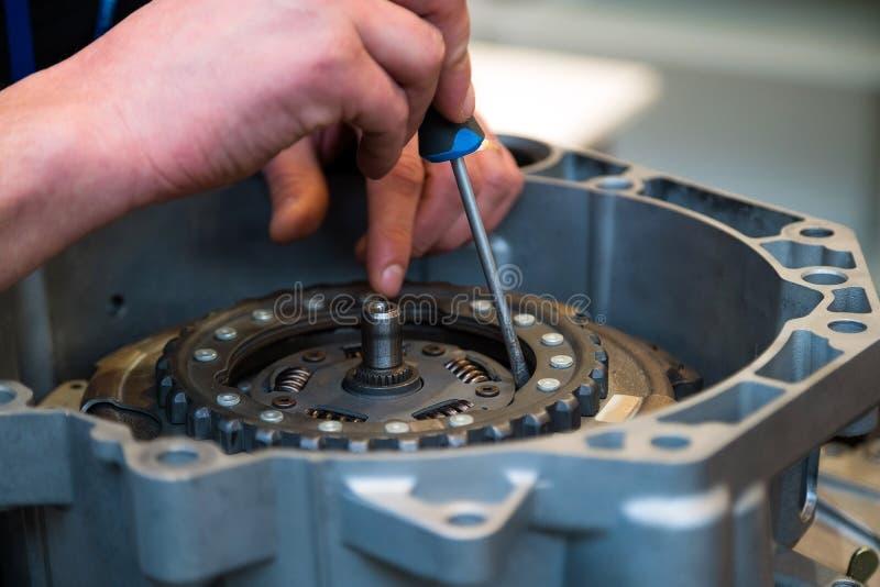 修理人定象与螺丝刀的汽车零件 他的车间的年轻技工 免版税库存照片