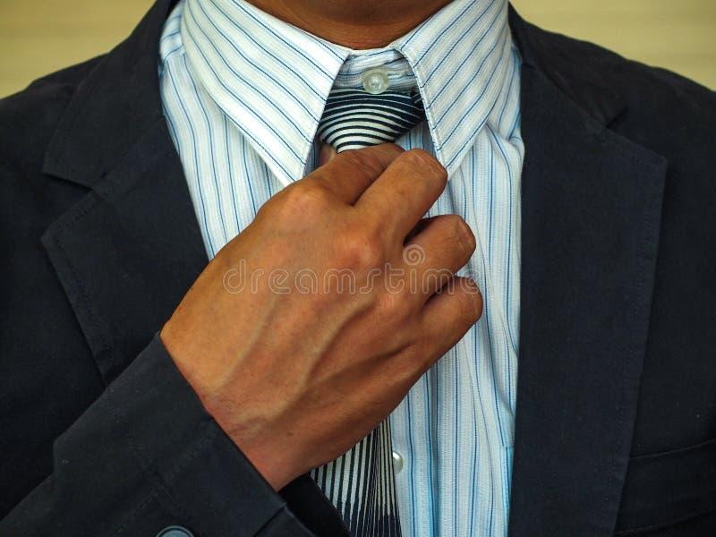 修理他的衣服的商人 免版税库存图片