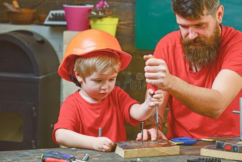 修理和车间概念 男孩,孩子繁忙在防护盔甲学会使用有爸爸的螺丝刀 父亲,父母 图库摄影