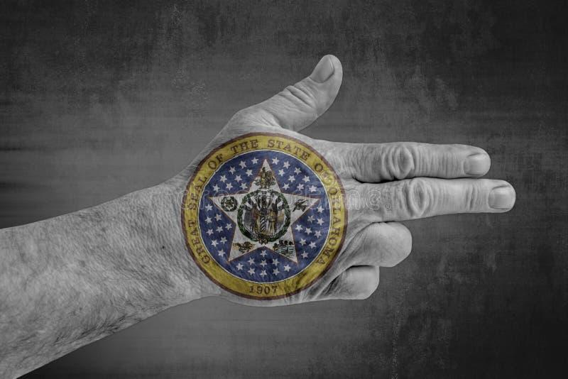 俄克拉何马状态在象枪的男性手上绘的封印旗子 免版税库存图片