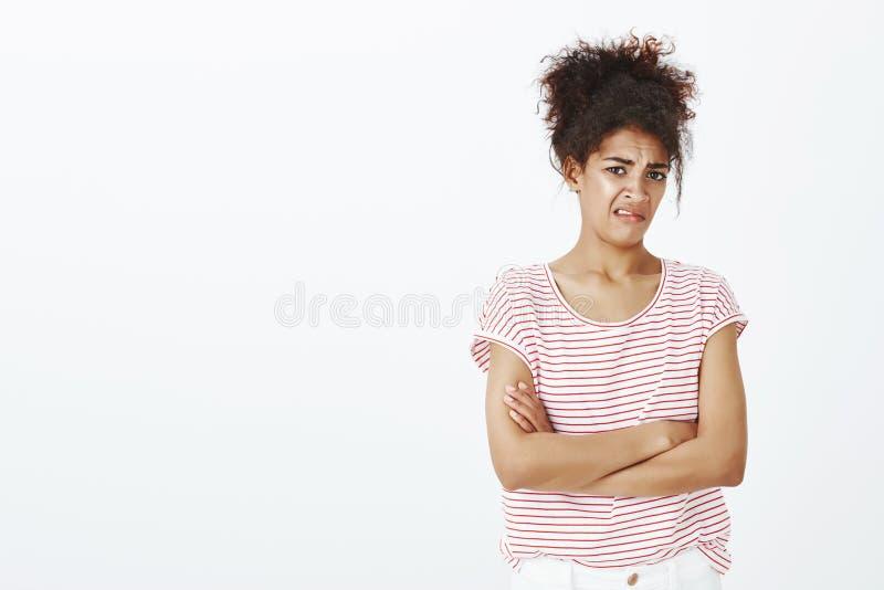 Äcklad oberörd attraktiv kvinna med lockigt hår i den randiga t-skjortan som rymmer händer korsade på bröstkorg och att se fotografering för bildbyråer