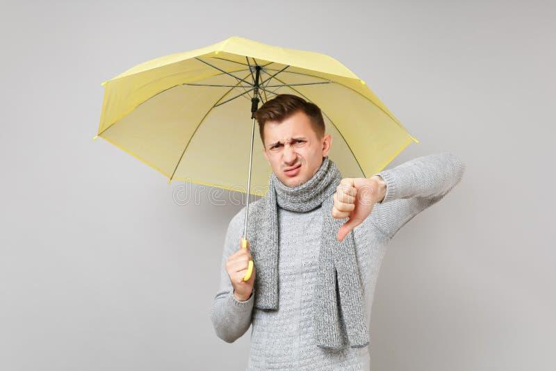 Äcklad ung man i den gråa tröjan, halsduk som rymmer den gula paraplyvisningtummen ner på grå bakgrund arkivfoton