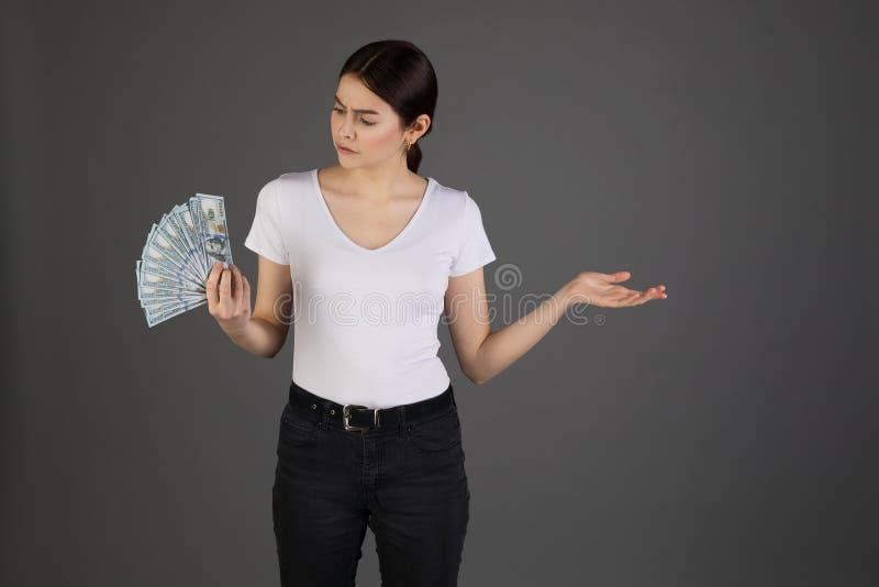 Äcklad uppriven affärskvinna i den vita t-skjortan med gruppen av pengar i hand royaltyfri foto