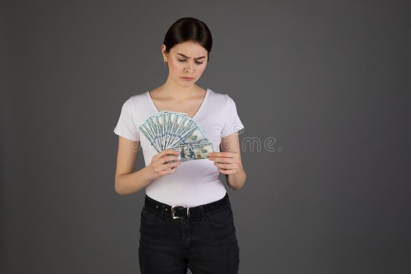 Äcklad uppriven brunettaffärskvinna i den vita t-skjortan med gruppen av pengar i hand arkivfoton