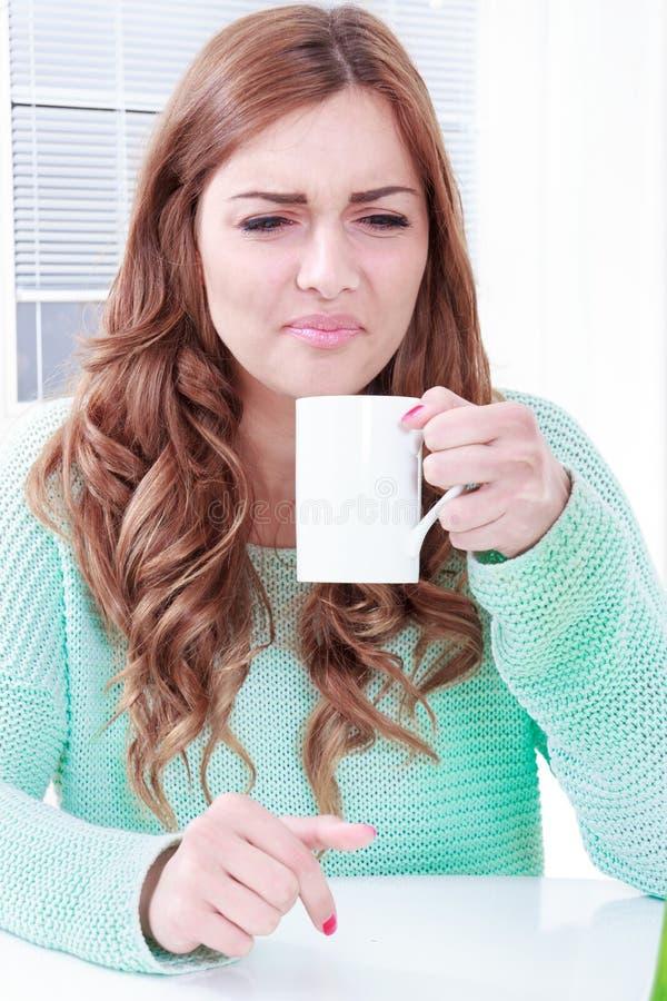 Äcklig lukt för kvinna av kaffe med framsidauttryck royaltyfri fotografi