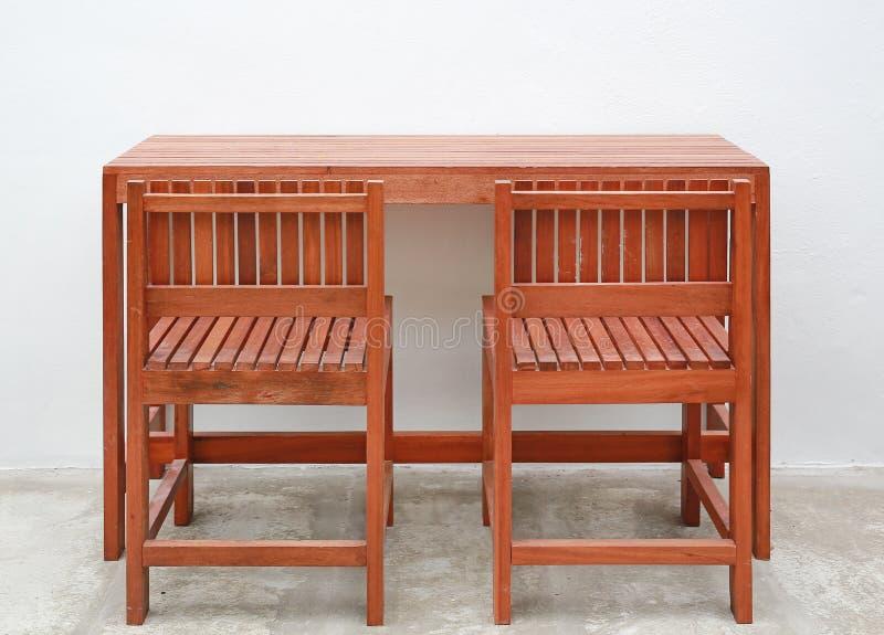 Ädelträmöblemang, inomhus trästol och tabelluppsättning mot väggbakgrund för vitt cement arkivfoton