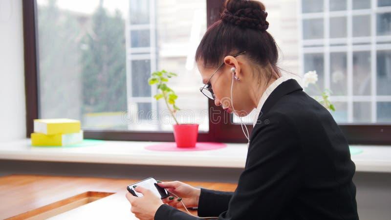 äganderätt för home tangent för affärsidé som guld- ner skyen till En kvinna i hörlurar som surfar internet på hennes telefon royaltyfri foto