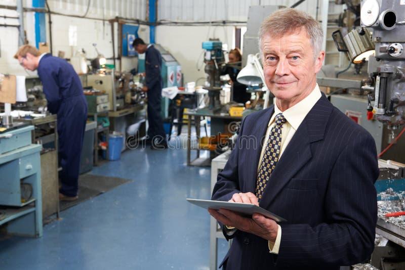Ägare av teknikfabriken med personalen i bakgrund royaltyfri foto