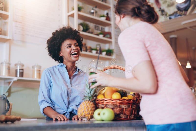 Ägare för fruktsaftstång som talar till den kvinnliga kunden arkivfoto