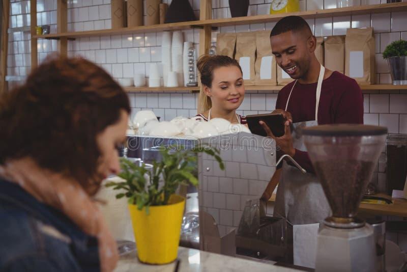 Ägare med den unga kvinnan som använder minnestavlan i kafé royaltyfria foton