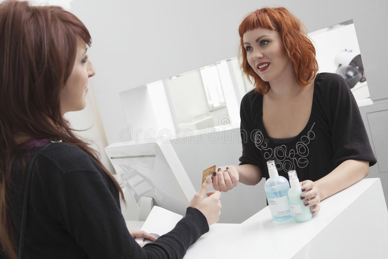 Ägare med kunden som inhandlar hårprodukter royaltyfri bild