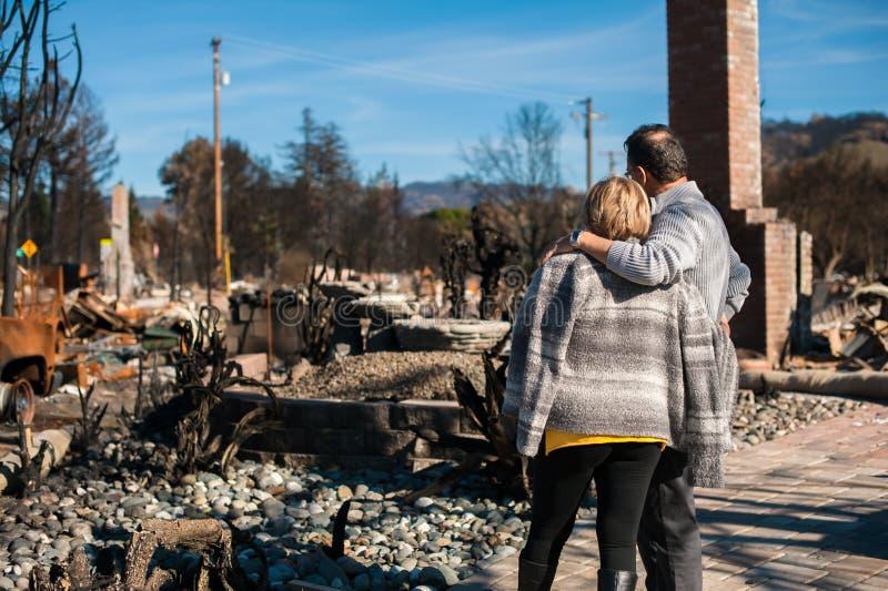 Ägare som kontrollerar det brända och fördärvade huset och gården efter brand arkivfoton