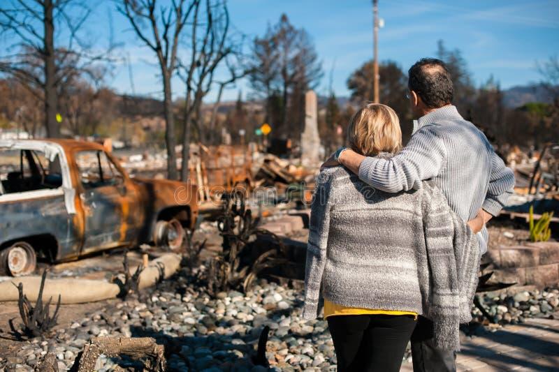 Ägare som kontrollerar det brända och fördärvade huset och gården efter brand royaltyfri foto