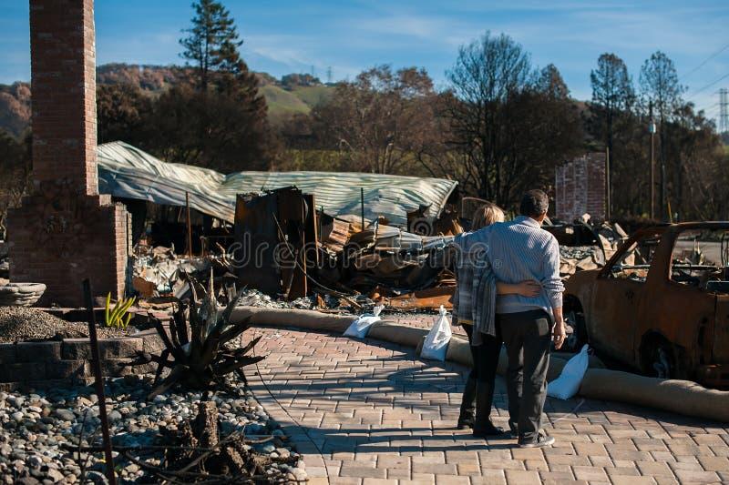 Ägare som kontrollerar det brända och fördärvade huset och gården efter brand arkivbilder