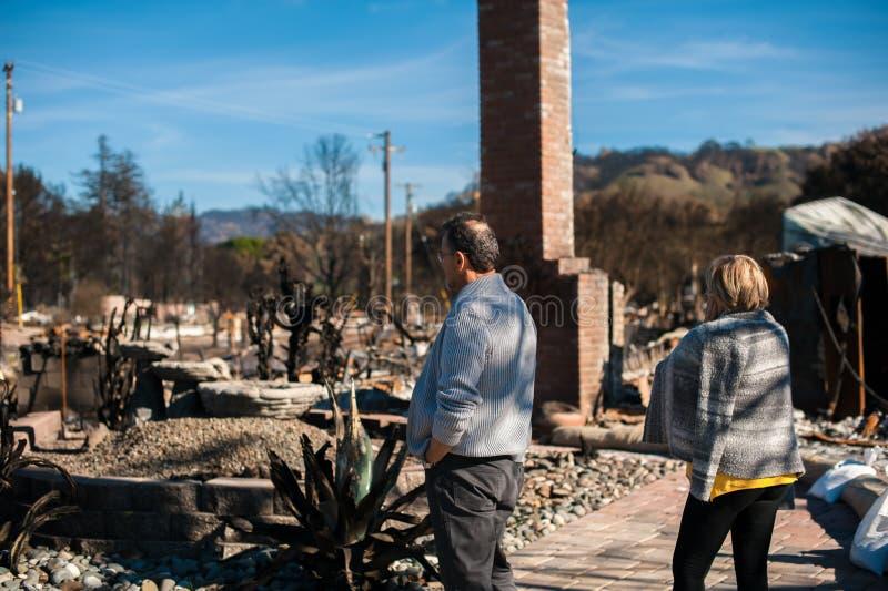 Ägare som kontrollerar det brända och fördärvade huset och gården efter brand royaltyfri fotografi