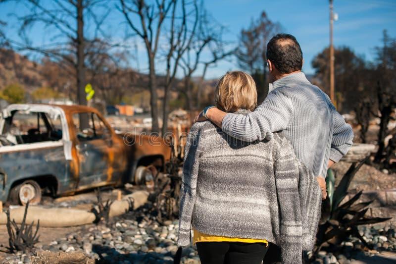 Ägare som kontrollerar det brända och fördärvade huset och gården efter brand royaltyfria foton