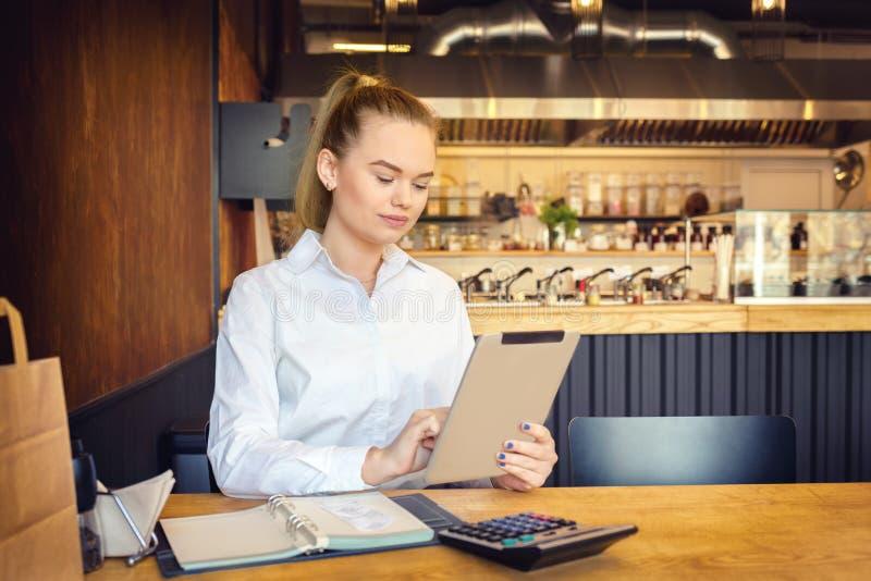 Ägare till små företag som använder digitala tabletter för att betala faktura och skatter och för att beräkna de finansiella kost arkivbild