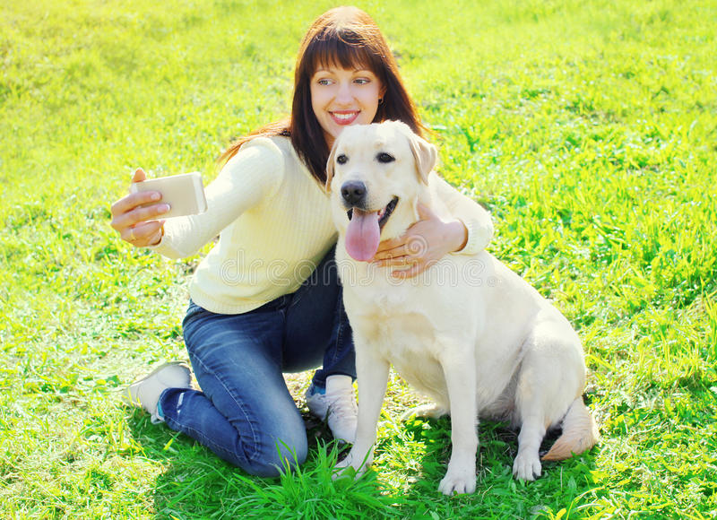 Ägarekvinna med den labrador retriever hunden som tar selfieståenden royaltyfri foto