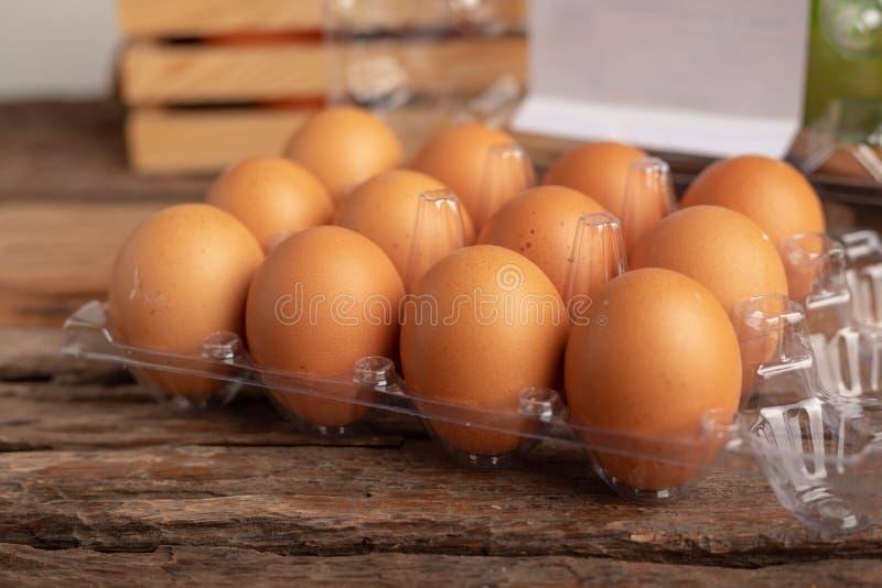 ägg av höna i en plast- ask som förläggas på en trätabell royaltyfria foton