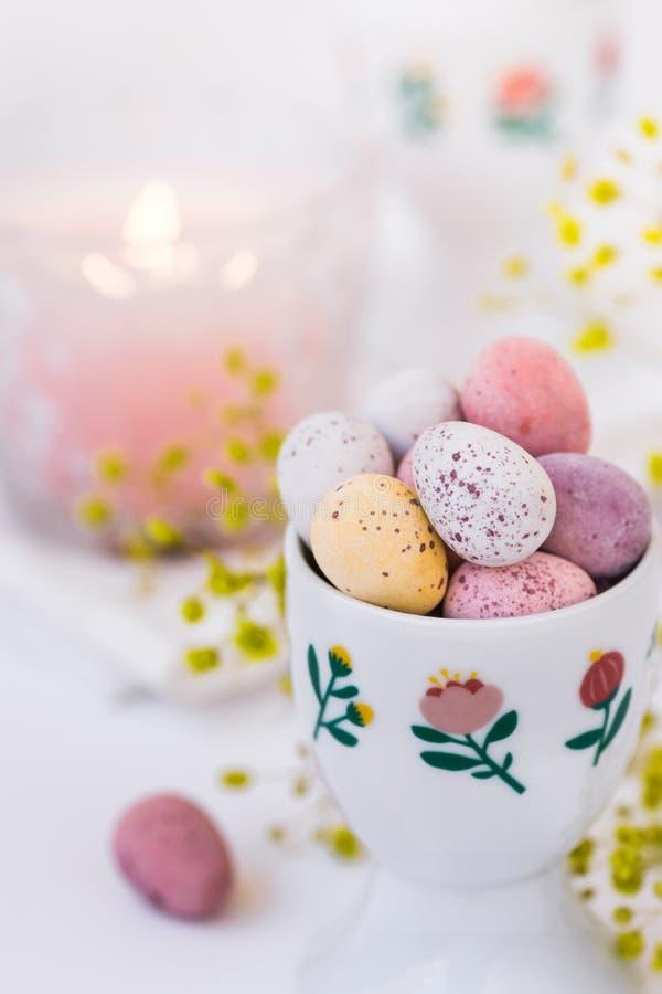 Ägg för påsk för chokladgodis färgade i keramisk koppbränningstearinljus, små blommor royaltyfri foto