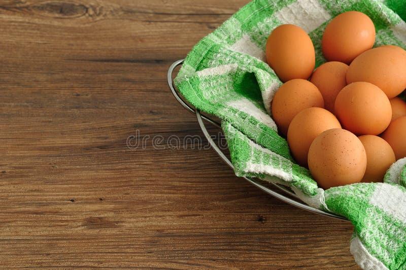 Ägg i en grön torkduk inom en trådkorg arkivfoton