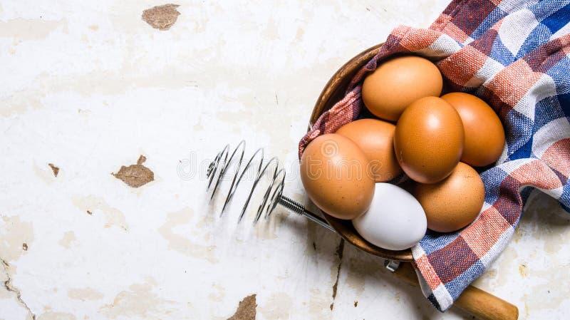 Ägg i en kopp med en torkduk och viftar royaltyfri foto
