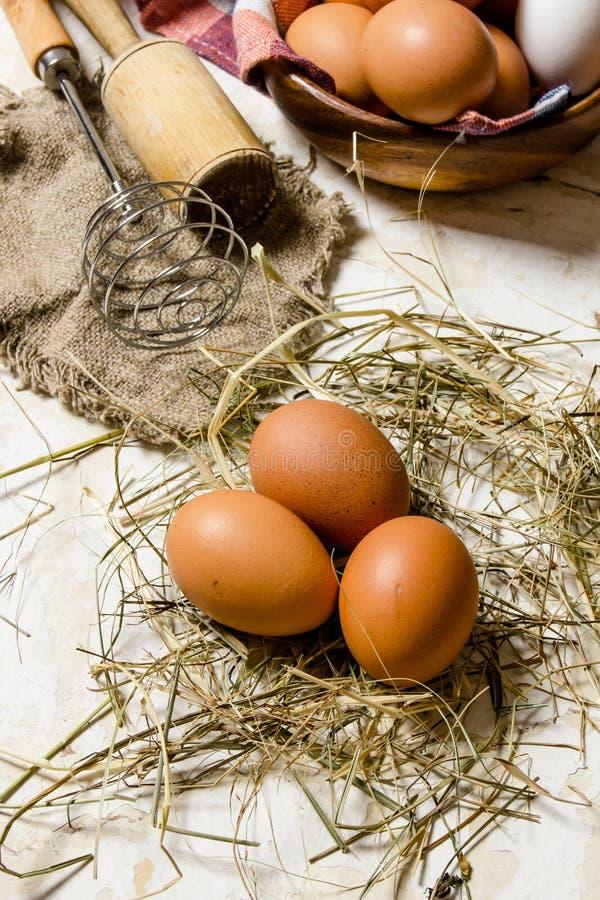 Ägg i en kopp med hö och hjälpmedel - vifta, mortelstöten royaltyfri fotografi