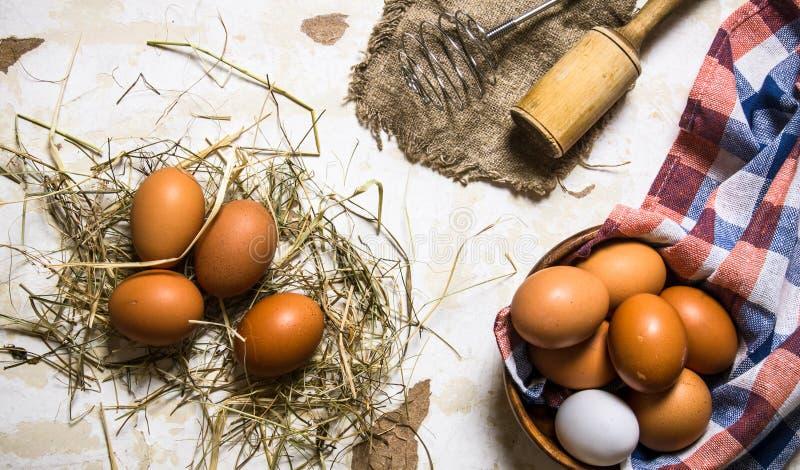 Ägg i en kopp med hö och hjälpmedel - vifta, mortelstöten arkivfoton