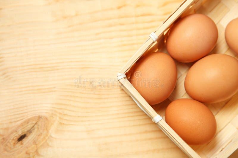 Ägg i en korg på en trätabellbakgrund arkivbilder