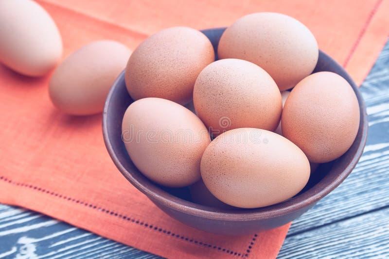 Ägg i en lera bowlar på en trätabell royaltyfri foto