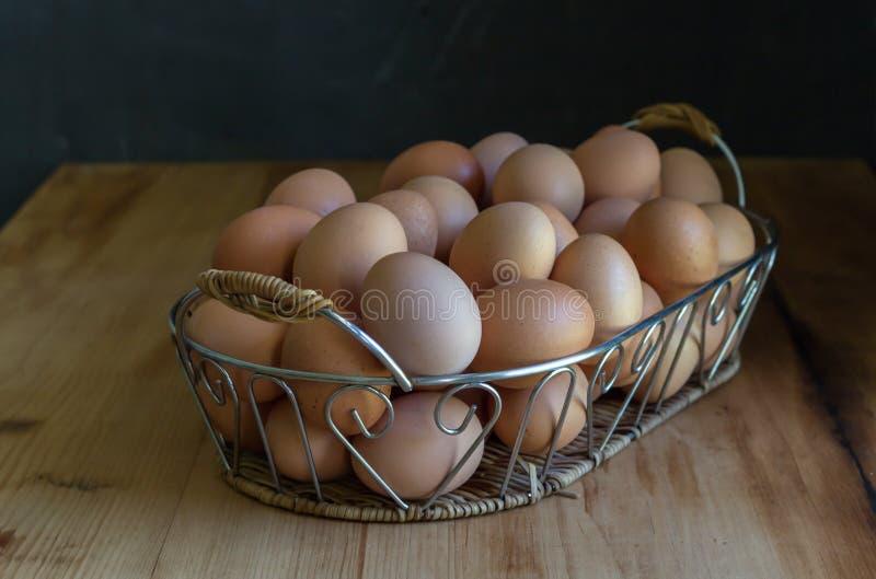 Ägg i försilvrar korgen på den lantliga trätabellen arkivfoto