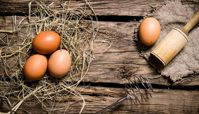 Ägg i höet med en mortelstöt trägrund tabell för djupfält royaltyfri foto