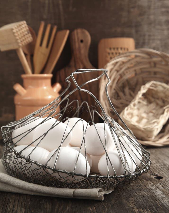 Ägg i korg- och kökmatlagningredskapen fotografering för bildbyråer