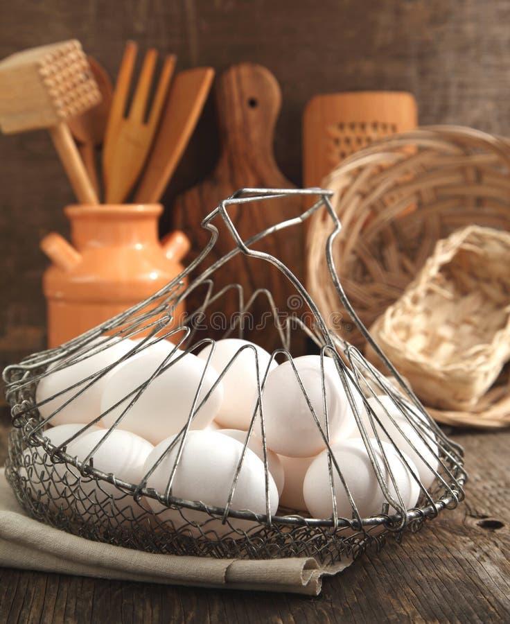Ägg i korg- och kökmatlagningredskapen royaltyfri fotografi