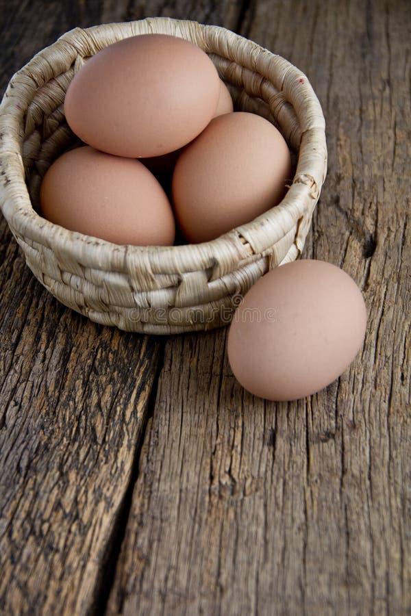 Ägg i korg på trä arkivfoto